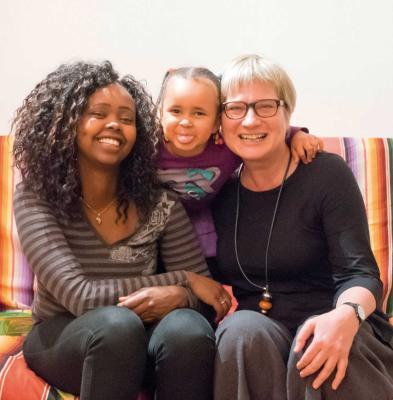 Patin und junge geflüchtete Mutter mit Kind am Sofa