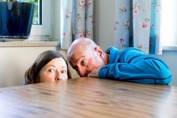 Zwei Rentner ducken sich unter einen Tisch
