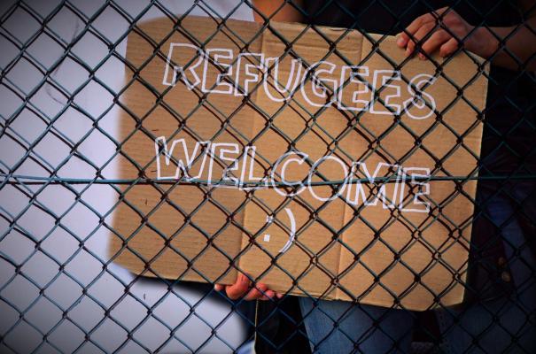 """Refugees Welcome"" Schild hinter Zaun"